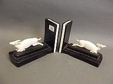 A good pair of Art Deco carved ebony and ivory bookends in the form of leaping deer, set with pearls, 5¾'' high, 8'' wide