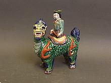 A highly coloured C19th Japanese porcelain figure of a seated man on a mythical beast, possibly Kutani, 6½'' high