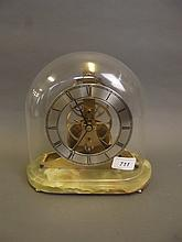 An early C20th brass skeleton clock under a glass dome, on a marble base, 8½'' high