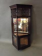 An Edwardian carved mahogany two door hanging corner cabinet with a mirrored back, 33½'' high
