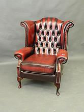 A buttoned leather wing armchair on mahogany cabriole supports