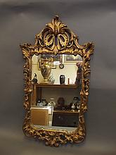 An early C20th ornate gilt composition wall mirror, 34'' x 19''