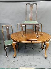 An Edwardian mahogany oval wind out dining table with two extra leaves, and four Queen Anne style dining chairs, table 76'' x 41'' extended