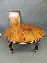 A Victorian mahogany circular extending dining table with one extra leaf, on fluted supports, 48'' diameter, 28'' high, leaf 17½'' wide