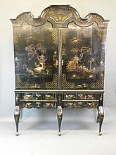 A large late C18th/early C19th Continental black lacquered cabinet on stand with gilt chinoiserie decoration, the top with two doors and shaped cornice on an interior with two drawers and later adaptations, the base of four shaped front drawers