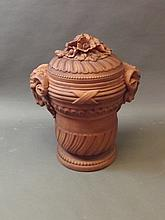 A large terracotta urn and cover with ram's head and foliate decoration, 22½'' high