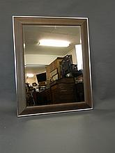 A contemporary silver leafed and leather framed cushion wall mirror with bevelled glass, 45½'' x 57½''