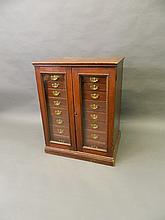A Victorian mahogany two door collector's cabinet, the two glazed doors enclosing nine graduated drawers, 26'' x 20'', 34'' high
