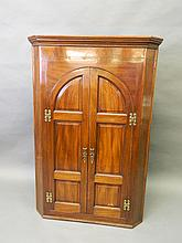 A good C19th mahogany inlaid double corner cupboard with arched panelled doors, the interior with shaped shelves and three spice drawers, 53'' high, 33'' wide