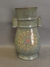 A celadon crackle glazed twin handled vase decorated with calligraphy and s