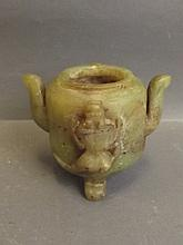 A Chinese green soapstone censer with raised dragon decoration, on tripod s