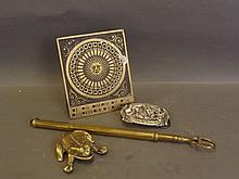 An extended brass toasting fork, a brass figure of a frog, a calendar, and