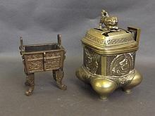 An Oriental bronze twin handled censer with raised decoration, on four shap