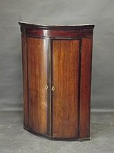 A George III oak and mahogany banded bow front hanging corner cupboard with