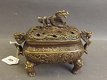 A Chinese bronze censer with twin dragon handles and pierced cover with dra