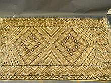 An Oriental hand knotted wool carpet with diamond designs on a beige field,