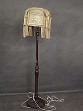 An early C20th walnut standard lamp with original tasselled parchment shade
