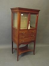 An Edwardian mahogany and satinwood banded music cabinet with a glazed uppe