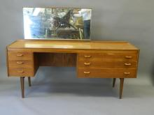 A 1970s teak pedestal dressing table with plain mirror back and asymmetric three drawer pedestals, on tapered supports, by Alfred Cox Furniture Co., 67