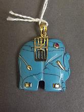 A turquoise and yellow metal pendant carved in the