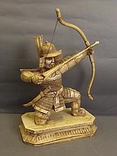 A faux ivory figure of a kneeling samurai archer,