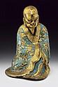 A partly enamelledand gilt bronze figure of Bodhidharma