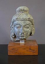 Carved Indian Stone Head of Deity.  On wooden sta