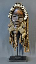 West African Dance Mask. Carved wood with shell.