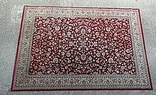 Rug /  Carpet : A machine made mid red ground rug with floral border and decorat