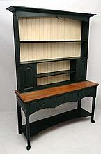 An early 20thC oak dresser painted with doors to cupboards flanking the open sec