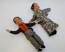 A Pair of early 20thC cloth dolls. Having printed faces and hand made clothing.