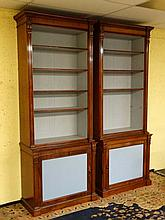A pair of early 19thC and later open mahogany bookcases with original panel