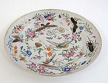 An 18thC famille rose Oriental style plate. Decorated with insects and butt
