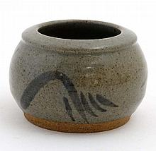 A signed studio pottery pot decorated with black marks on a grey/green grou