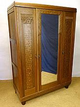 A Continental oak Art Deco triple wardrobe with