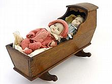 A 19thC wooden doll's cradle on rockers, with two