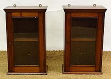 A pair of glazed front wall hanging cabinets