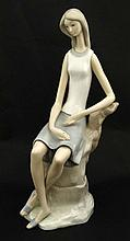 A Lladro figure modelled as a lady sat upon a rock