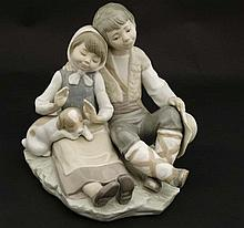 A Lladro figure group modelled as a seated boy and