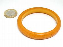 An Art Deco amber coloured celluloid bangle