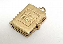 A 9ct gold charm formed as a Holy Bible opening to