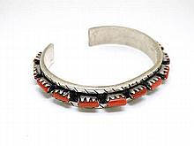 A white metal bracelet set with coral like hard