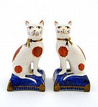 A pair of Staffordshire style cats having iron red