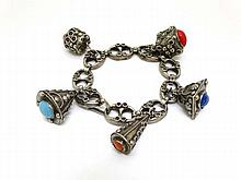 A silver plate charm bracelet set with various