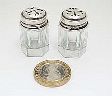 A pair of glass and Continental silver pepperettes