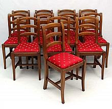A long set of 12 late 20thC oak dining chairs with upholster
