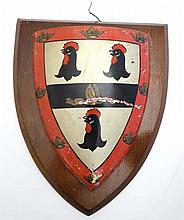An early 20thC Armorial tole-peint shield mounted upon a mah