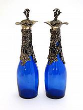 A pair of Victorian style blue glass bottles with grapevine