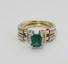 A 14ct gold ring set with central emeralds flanked by 4 diam