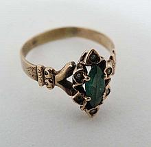 A gilt metal ring set with central emerald bordered by 5 see